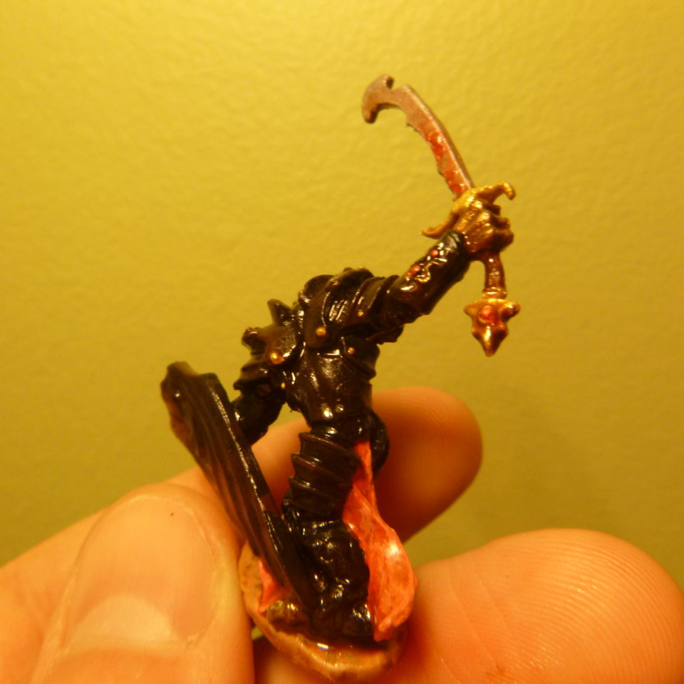 The backside of Bones' Dragonman Warrior miniature painted bronze, black, and gold