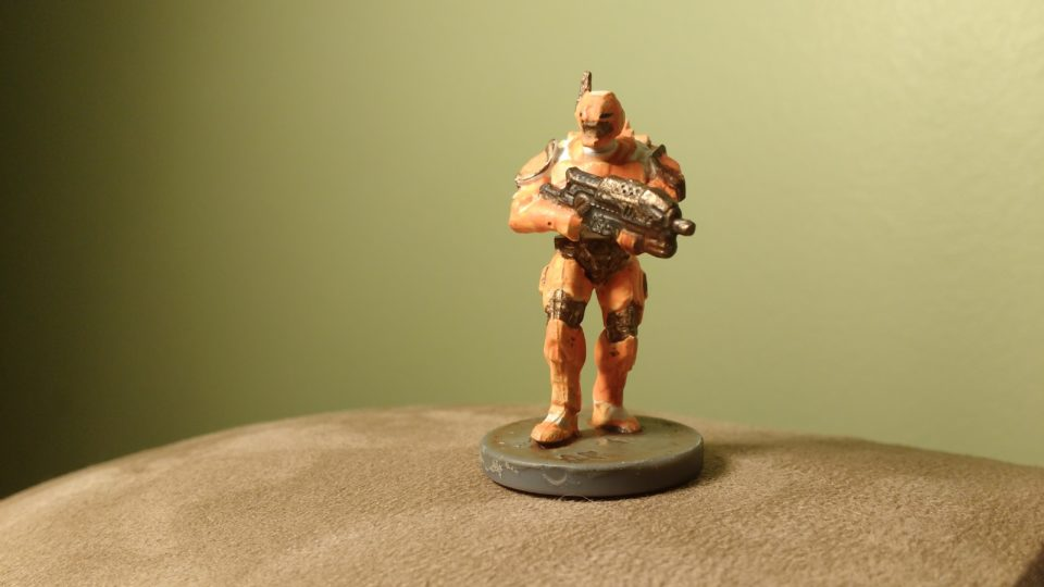 An Enforcer miniature from Mantic Entertainment's Deadzone game. This one carries a Machine Gun and is painted Orange and White.