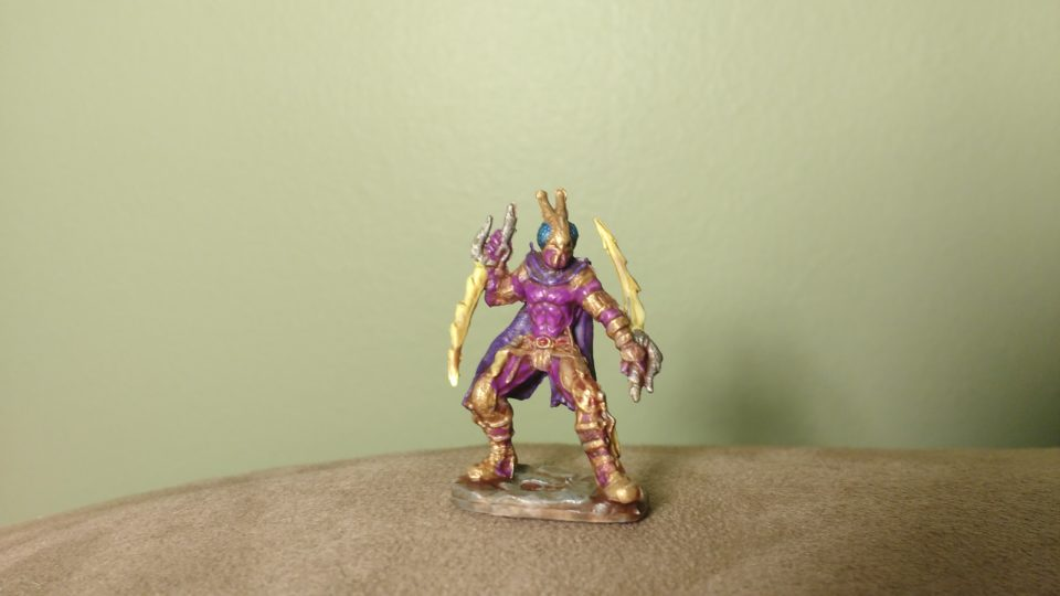 The Red Mantis Assassin miniature from Reaper Bones painted gold and purple.